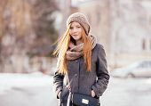 Winter portrait of a cute redhead lady in grey coat and scarf outdoors
