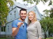 love, people, real estate, home and family concept - smiling couple showing key over house background