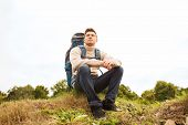 adventure, travel, tourism, hike and people concept - man with backpack sitting on ground