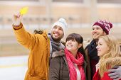 people, friendship, technology and leisure concept - happy friends taking selfie with smartphone on skating rink