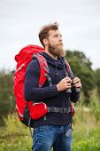adventure, travel, tourism, hike and people concept - man with red backpack and binocular outdoors