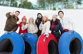 winter, leisure, sport, friendship and people concept - group of smiling friends with snow tubes showing thumbs up outdoors