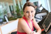 Portrait of smiling fitness girl leaning on treadmill