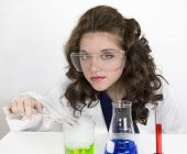 pic of tong  - Teenage girl wearing lab coat and doing a science experiment with green and blue liquid with tongs - JPG
