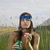 Thoughtful Woman Blowing Soap Bubbles