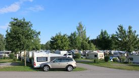 picture of caravan  - Many caravans on a camping site, between the trees.