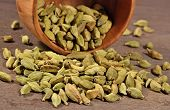 stock photo of cardamom  - Cardamom seeds in a wooden bowl close up - JPG