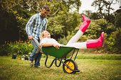 foto of wheelbarrow  - Happy couple playing with a wheelbarrow on a sunny day - JPG