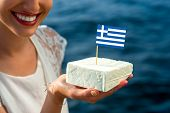 stock photo of greeks  - Holding in hand traditional greek feta cheese with greek flag on blue sea background - JPG