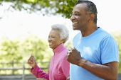 image of senior adult  - Senior African American Couple Jogging In Park - JPG