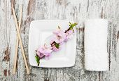 picture of chopsticks  - plate chopsticks towel and sakura branch on a wooden background - JPG