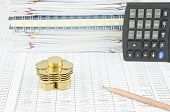 picture of piles  - Pile of gold coins and brown pencil with calculator on finance account have pile of paperwork and notebook as background - JPG