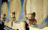 image of tapping  - Three oak wooden barrels with a focus on taps - JPG