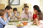 stock photo of extend  - Extended Hispanic Family Saying Prayers Before Meal At Home - JPG