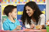 stock photo of pupils  - Elementary Age Pupil In Art Class With Teacher - JPG