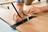 foto of laminate  - Close-up Of A Worker Drawing A Mark On Laminate Using Ruler ** Note: Shallow depth of field - JPG