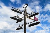 picture of crossroads  - Blank black crossroad signs different directions on cloudy blue weather - JPG