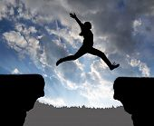 stock photo of gap  - Silhouette the girl jumping over the gap at sunset - JPG