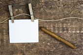 foto of clotheslines  - white paper sign hanging on clothesline with clothespins on rustic wooden background with a cigar - JPG