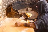 picture of arabic woman  - Old Arab woman prepares bread in a Bedouin village - JPG