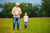 picture of grandfather  - grandfather and grandson walking through the green field with puppy in hands - JPG