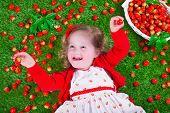 stock photo of peeking  - Child eating strawberry - JPG
