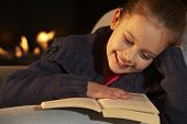 image of 7-year-old  - Portrait 7 year old girl reading by firelight - JPG