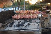 picture of brazier  - Roasting shish kebab on a brazier at an outdoor cafe horizontal - JPG