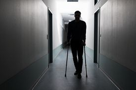 image of crutch  - Silhouette Of Disabled Man Walking With Crutches In Hospital - JPG