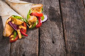 image of sandwich wrap  - Chicken wrap sandwiches on wooden background with blank space - JPG