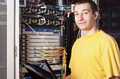 stock photo of console-mirror  - The engineer in datacenter near telecomunication equipment - JPG