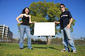 Young couple holding white billboard