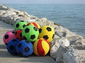 Colorful Balloons Playing On The Rocks Near The Sea To Italian