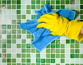 stock photo of house cleaning  - Hand in yellow protective glove  cleaning mosaic wall - JPG