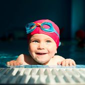 Happy little girl looking out from swimming pool