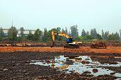 reflection of Excavator Loader with backhoe standing in sandpit