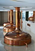 Line of three brewing vessels in brewery.