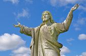 stock photo of irish moss  - Pre 1900 stone statue of Jesus weather beaten with arms reaching up to heaven against bright blue sky with clouds from a grave in the famous landmark Milltown Cemetery Belfast which is the largest Catholic burial ground in Belfast and synonymous with Iris - JPG