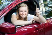 Bela loira adolescente sentado em seu novo carro, segurando as chaves.