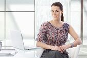 Portrait of attractive office assistant woman sitting at desk with laptop, smiling at camera confide poster