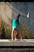 Woman Doing Yoga Outdoors In Three Leg Downward Facing Dog Pose