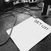 Rock band blank set list on a stage with guitar pedals and cables - Black and White grainy instagram poster