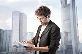 foto of young men  - Young man using a tablet pc with cityscape in the background - JPG