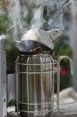 picture of smoker  - Antique bee smoker at work - JPG