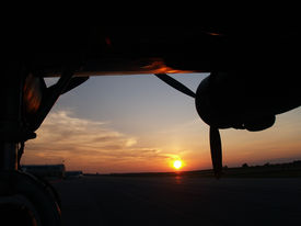 foto of b24  - Wing and engines of a B24 Liberator silhoutted against a sunset - JPG