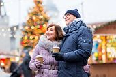 love, winter holidays and people concept - happy senior couple with takeaway coffee at christmas mar poster