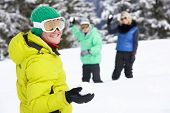 Group Of Young Friends Having Snowball Fight On Ski Holiday In Mountains