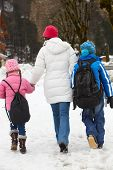 Mother Walking Two Children To School Along Snowy Street In Ski Resort