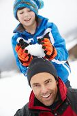 Young Boy About To Drop Snowball On Fathers Head
