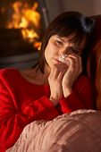 Sick Woman With Cold Resting On Sofa By Cosy Log Fire